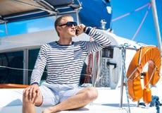Giovane ed uomo bello che si rilassa su una barca a vela Fotografia Stock Libera da Diritti