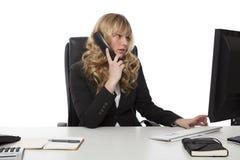 Giovane elaborazione multitask della donna di affari Immagini Stock Libere da Diritti