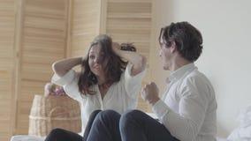 Giovane emozionale e calcio o baseball di sorveglianza della donna che si siede sul letto La relazione fra l'uomo e la donna stock footage
