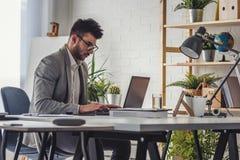 Giovane enterpreneur moderno dell'uomo d'affari che si siede nel suo ufficio che lavora ad un computer fotografia stock