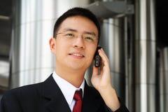 Giovane esecutivo asiatico che comunica sul handphone Fotografia Stock Libera da Diritti