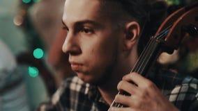 Giovane esecutore con la coda di cavallo in camicia di plaid che gioca violoncello con l'archetto archivi video