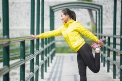 Giovane esercitazione asiatica della donna all'aperto in rivestimento al neon giallo, allungante Immagine Stock