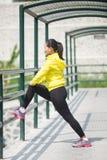 Giovane esercitazione asiatica della donna all'aperto in rivestimento al neon giallo, stre Fotografie Stock