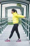Giovane esercitazione asiatica della donna all'aperto in rivestimento al neon giallo, stre Fotografia Stock