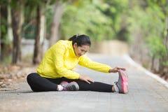 Giovane esercitazione asiatica della donna all'aperto in rivestimento al neon giallo, stre Fotografia Stock Libera da Diritti