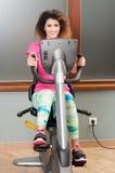 Giovane esercitazione femminile attraente sulla bici e sullo smili stazionari Fotografia Stock Libera da Diritti