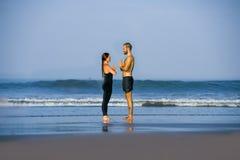 Giovane esercizio di pratica di acroyoga delle coppie attraenti e belle dell'acrobata concentrato tenendo yoga practiing dell'equ fotografia stock
