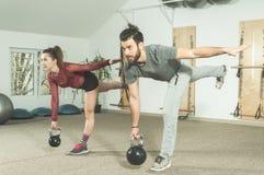 Giovane esercizio nella palestra, fuoco selettivo di forma fisica del kettlebell di allenamento delle coppie Fotografia Stock