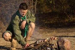 Giovane esploratore maschio Grilling Sausages al campo fotografia stock