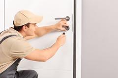 Giovane fabbro che installa un fissare una porta Immagini Stock