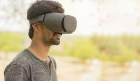 Giovane facendo uso dei vetri di una cuffia avricolare di VR fuori fotografia stock libera da diritti