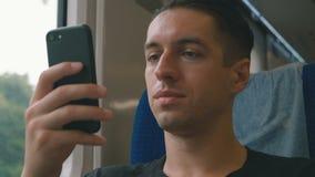 Giovane facendo uso del suo smartphone, legante e facente scorrere durante il giro del treno stock footage