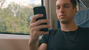 Giovane facendo uso del suo smartphone, legante e facente scorrere durante il giro del treno video d archivio