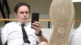 Giovane facendo uso di Smartphone nel luogo di lavoro stock footage