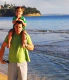 Giovane famiglia alla spiaggia di mattina Immagini Stock