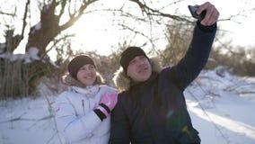 Giovane famiglia allegra per fare lo smartphone del selfie Madre, padre e figlio Giorno di inverno congelato e soleggiato archivi video