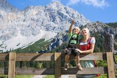 Giovane famiglia bavarese in un bello paesaggio della montagna Fotografia Stock