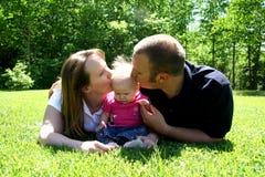 Giovane famiglia che bacia bambino Fotografie Stock Libere da Diritti