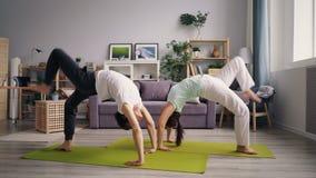 Giovane famiglia che fa ginnastica a casa che si esercita nella posizione del granchio sul pavimento stock footage