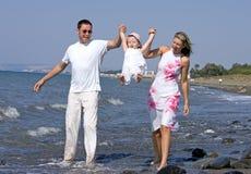 Giovane famiglia che gioca con la figlia sulla spiaggia in Spagna fotografie stock libere da diritti