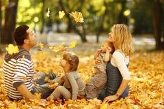 Giovane famiglia che gioca nel parco di autunno all'aperto fotografia stock