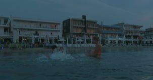 Giovane famiglia che gode del bagno di mare nella sera stock footage