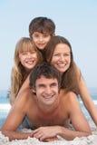 Giovane famiglia che ha divertimento sulla festa della spiaggia Fotografie Stock Libere da Diritti