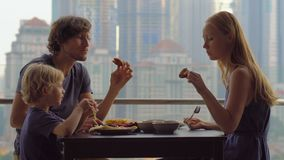 Giovane famiglia che mangia una prima colazione, pranzo sul loro balcone in un grattacielo con una vista su una città di tutto de stock footage
