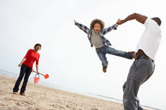 Giovane famiglia che si distende sulla festa di campeggio della spiaggia Fotografie Stock Libere da Diritti