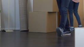 Giovane famiglia che si muove verso il nuovo appartamento, scatole di trasporto con roba, proprietà d'acquisto video d archivio