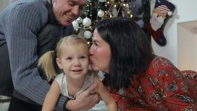 Giovane famiglia che si trova su una coperta sotto l'albero di Natale stock footage