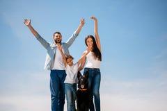 Giovane famiglia che sta insieme al cane e che sorride alla macchina fotografica all'aperto Immagine Stock
