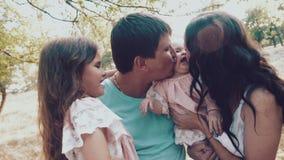 Giovane famiglia con due piccole figlie nella natura Famiglia felice sul primo piano della natura archivi video
