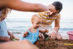 Giovane famiglia con i bambini del bambino che giocano sulla spiaggia sulla vacanza estiva fotografia stock libera da diritti