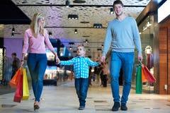 Giovane famiglia con i sacchetti della spesa Fotografie Stock