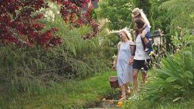 Giovane famiglia con il canestro dopo il picnic che cammina giù le scale fuori in parco verde video d archivio