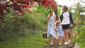 Giovane famiglia con il canestro dopo il picnic che cammina giù le scale fuori in parco verde archivi video