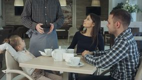 Giovane famiglia con la figlia cenando al ristorante Generi il cameriere di chiamata in modo che la sua moglie faccia l'ordine Fotografia Stock