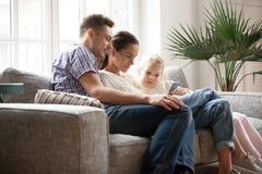 Giovane famiglia con la figlia che usando cellulare app che si siede sullo strato Fotografia Stock Libera da Diritti