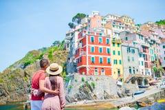 Giovane famiglia con la grande vista al vecchio villaggio Riomaggiore, Cinque Terre, Liguria, Italia Vacanza italiana europea Immagini Stock