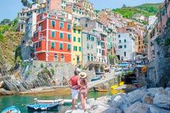 Giovane famiglia con la grande vista al vecchio villaggio Riomaggiore, Cinque Terre, Liguria, Italia Vacanza italiana europea Fotografie Stock