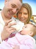 Giovane famiglia con la neonata in una sosta di autunno immagini stock libere da diritti