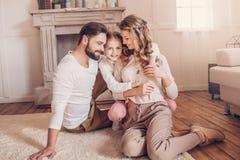 Giovane famiglia con un bambino che si siede sul tappeto e che abbraccia a casa Fotografia Stock Libera da Diritti