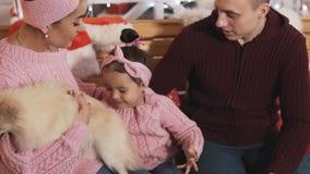 Giovane famiglia felice alla decorazione di natale con il derivato ed il cane Concetto 'nucleo familiare' archivi video