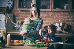 Giovane famiglia felice, bella madre con due bambini, ragazzo prescolare adorabile e bambino in imbracatura che cucinano insieme  Immagini Stock