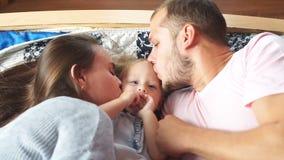 Giovane famiglia felice che abbraccia e che bacia nella camera da letto archivi video