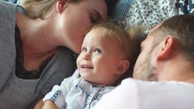 Giovane famiglia felice che abbraccia e che bacia nella camera da letto video d archivio
