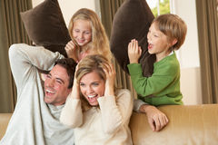 Giovane famiglia felice che ha divertimento con i cuscini sul sofà Fotografia Stock