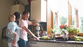 Giovane famiglia felice che prepara prima colazione nella cucina Movimento lento stock footage
